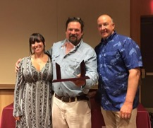 "Krissy Wejebe (left) of the Jose Wejebe Memorial Foundation and Larry Rencken of Raymarine (right) present the Jose Wejebe Saltwater MVP Award to Carter ""Big Boy"" Andrews"